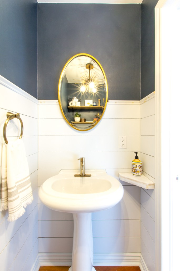 Nautical powder room with white shiplap and brass accents