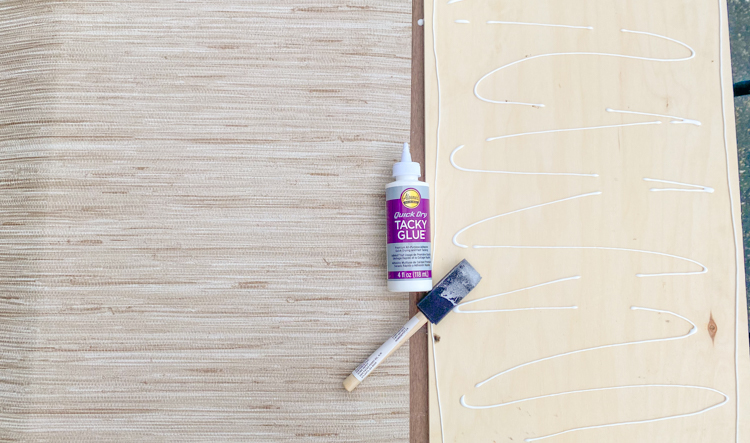 Use glue to adhere the wallpaper to the plywood panel