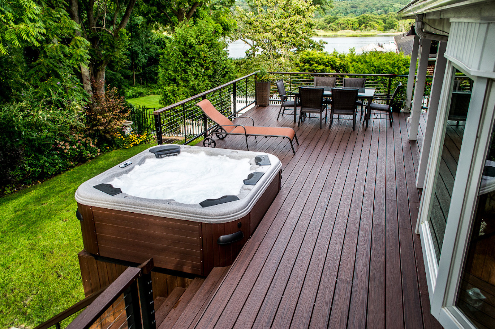 medium resolution of wood deck with hot tub overlooking lush green area