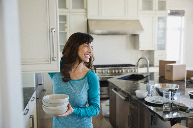 Woman putting away dishes in new home