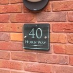 glass slate stainless steel house sign on a wall