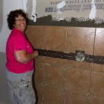 Mom putting up tiles.