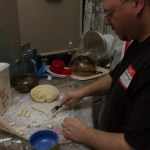 Lionel divides the dough into pieces.
