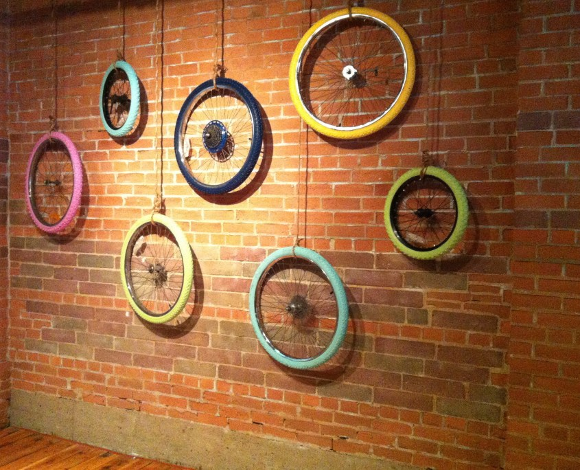 Painted bicycle wheels - art hanging in the Mercer building - Startup Edmonton