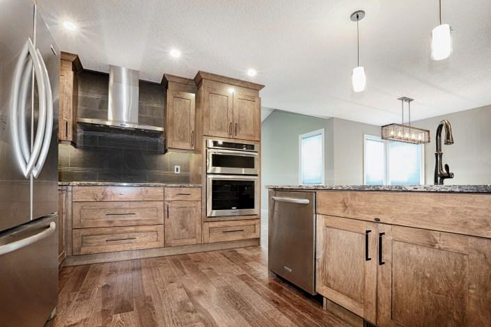 stainless steel hood fan, double ovens. By House of J Interior Design. Edmonton, Alberta.