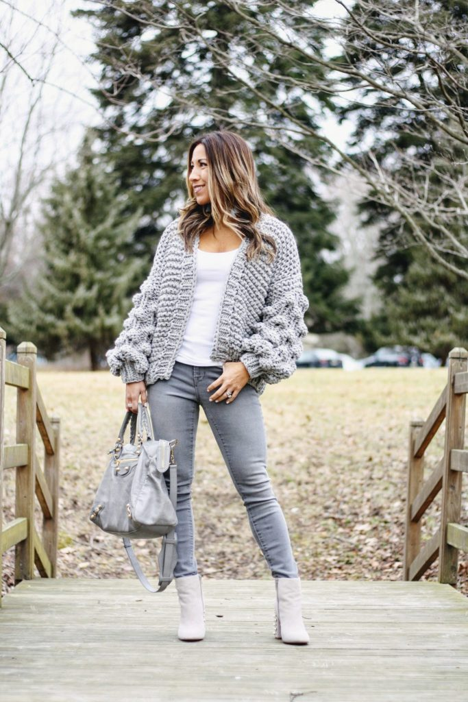 Old Navy Rockstar Jeans review featured by top New Jersey fashion blog, House of Leo: image of a woman wearing Old Navy Rockstar jeans, Goodnight Macaron chunky cardigan, Steve Madden ankle booties, Express tank top and BP earrings