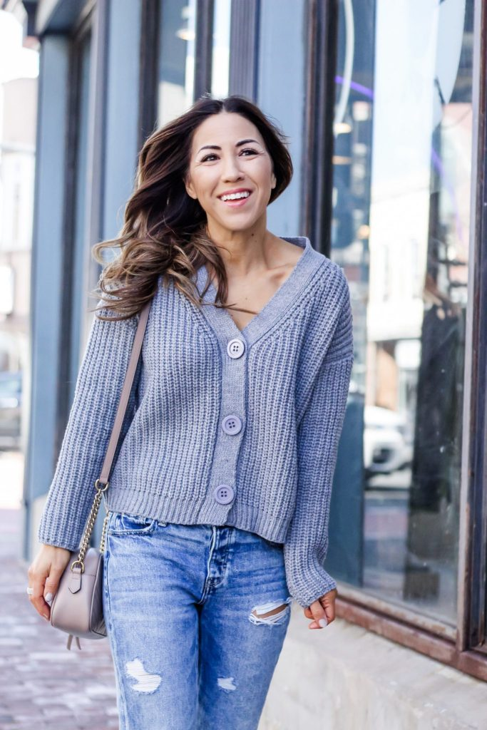 Latest Spring Fashion with Yoox by top US fashion blog, House of Leo Blog: image of a woman wearing a gray cropped cardigan, blue platform VANS sneakers, Bart's beanie and American Eagle tomgirl jeans