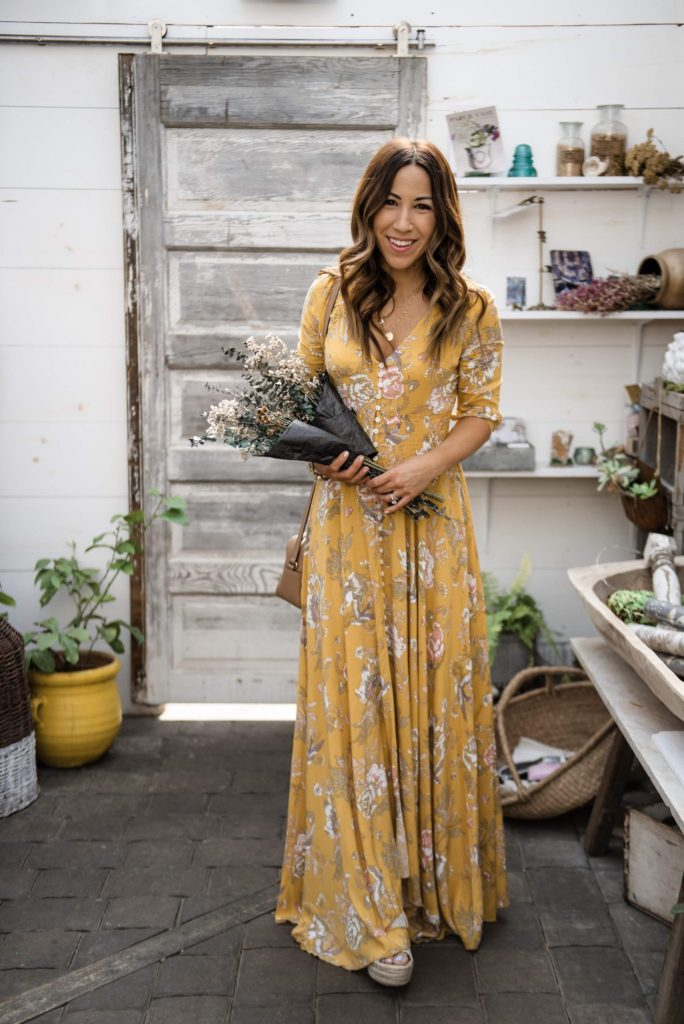 The Best Yellow Dresses for Spring by top US fashion blog, House of Leo Blog: image of woman wearing a yellow floral maxi dress from Chicwish, Old Navy denim jacket at The French Market in Rumson