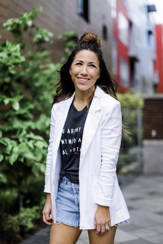 Evereve Mother's Day Sale by top US fashion blog, House of Leo Blog: image of woman wearing Level 99 white blazer, black graphic tank, Agolde Parker denim shorts