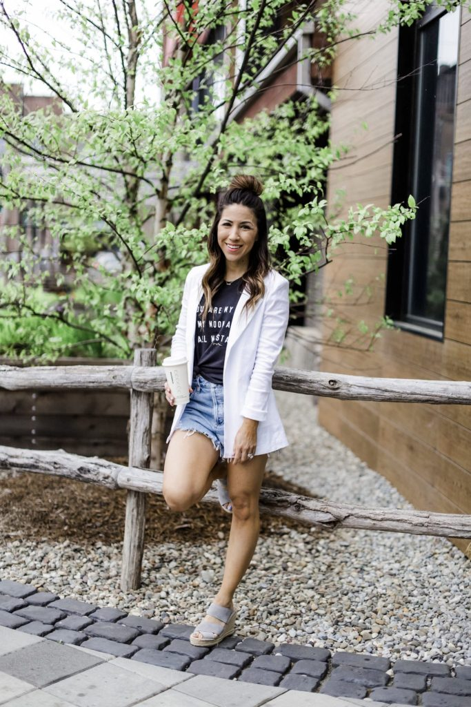 Evereve Mother's Day Sale by top US fashion blog, House of Leo Blog: image of woman wearing Level 99 white blazer, black graphic tank, Agolde Parker denim shorts and Kenneth Cole wedge espadrilles