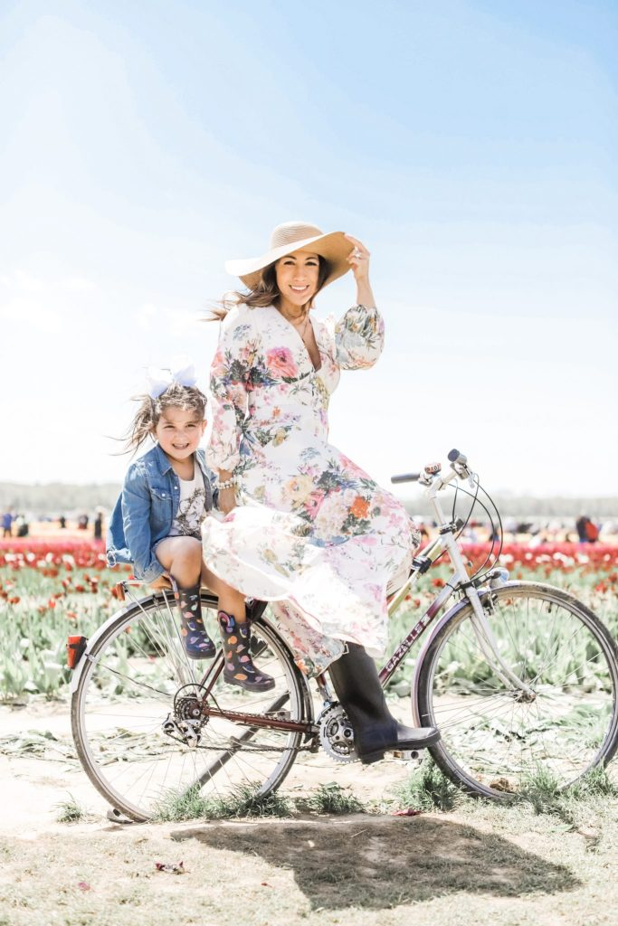2 Year Blogiversary: 5 Top Tips on How to Grow Your Blog in a Couple of Years by top US fashion blog, House of Leo Blog: image of woman and child at Holland Ridge Tulip Farm on a bicycle wearing a Chicwish floral dress and straw hat