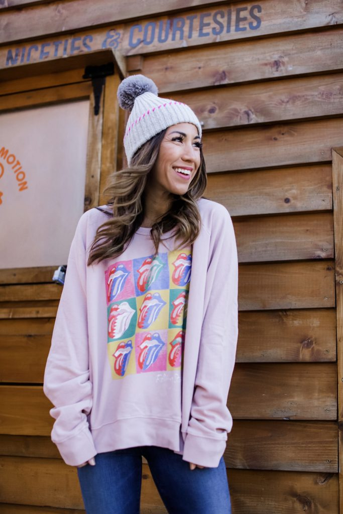 Holiday Outfit Ideas From Evereve by top US fashion blog, House of Leo Blog: image of woman wearing pink Rolling Stones sweatshirt