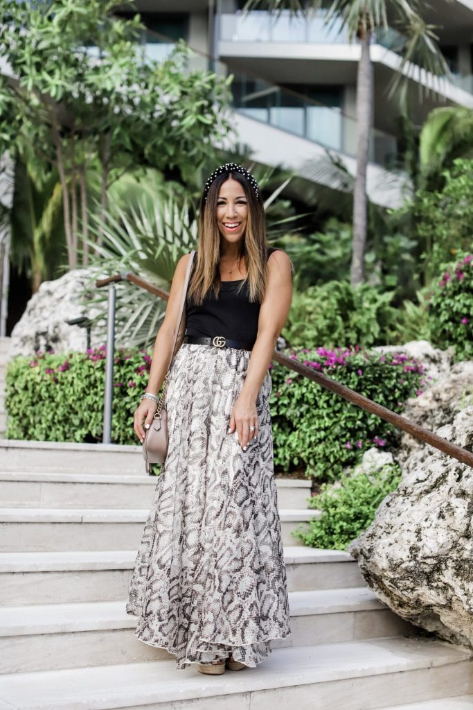 All Season Snakeskin Skirt in Grand Cayman by top US fashion blog, House of Leo Blog: image of woman in snakeskin maxi skirt, black bodysuit and pearl headband