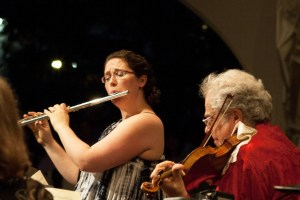 Woman plays flute with her father who is playing violin.