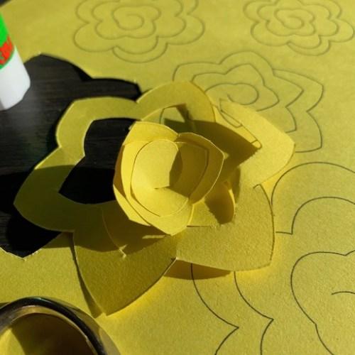 lijm de papieren bloem terwijl je deze wikkelt