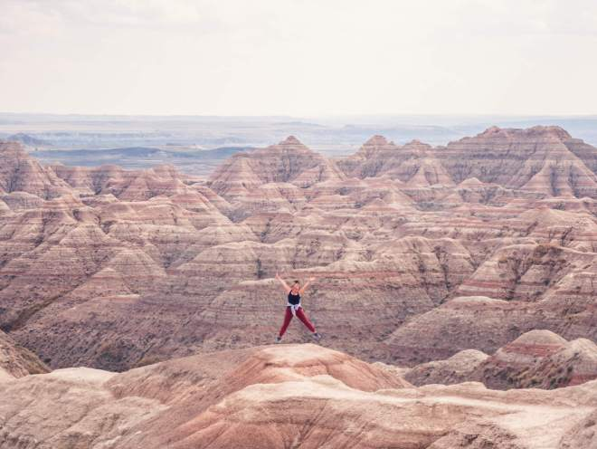 Jumping for joy by the sharp rock formations in Badlands National Park