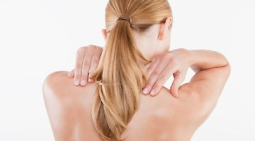 Girl holding shoulders due to stiff neck