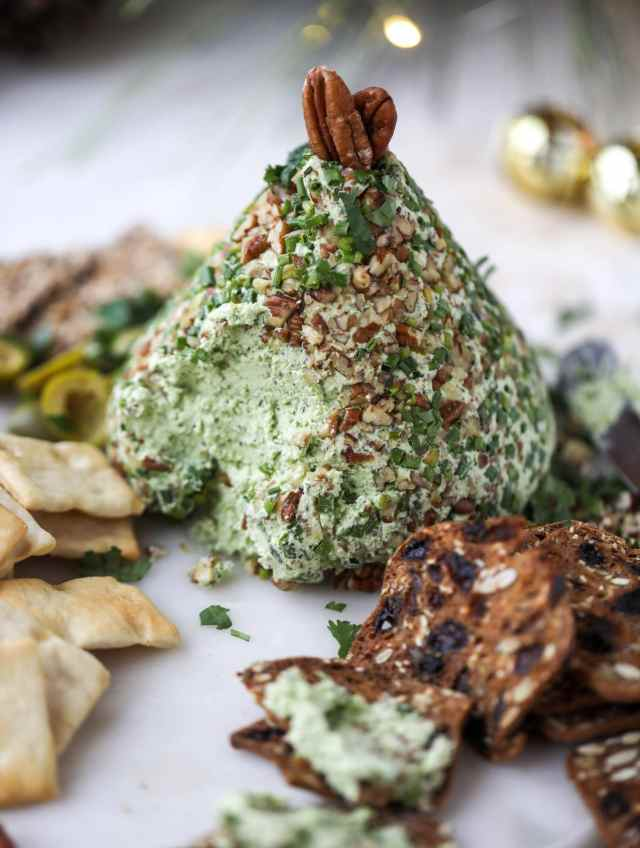 This green goddess cheese ball is the perfect party snack! You can make it ahead of time and shape it into a cute tree for a festive look. Serve it with crispy crackers and pita chips! I howsweeteats.com #greengoddess #cheeseball
