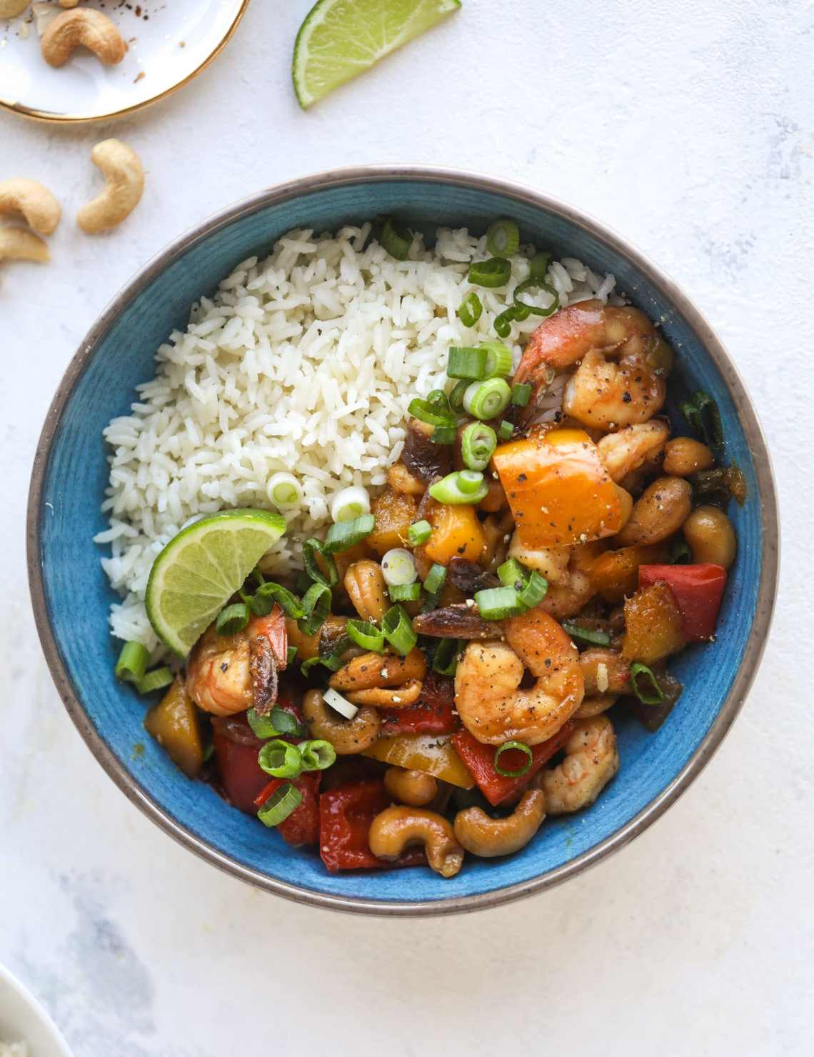 This cashew shrimp stir fry is a super simple weeknight meal! Made with bell peppers and mango, it is delicious over rice and comes together in 25 minutes. I howsweeteats.com #cashew #shrimp