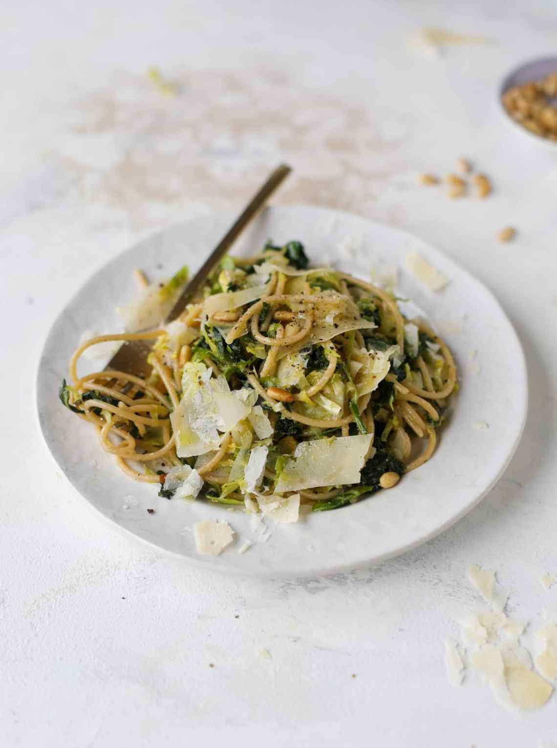 This brussels spaghetti with kale, parmesan and pine nuts is a super flavorful, quick and easy weeknight meal. You can add in a protein if you wish! I howsweeteats.com #brussels #spaghetti