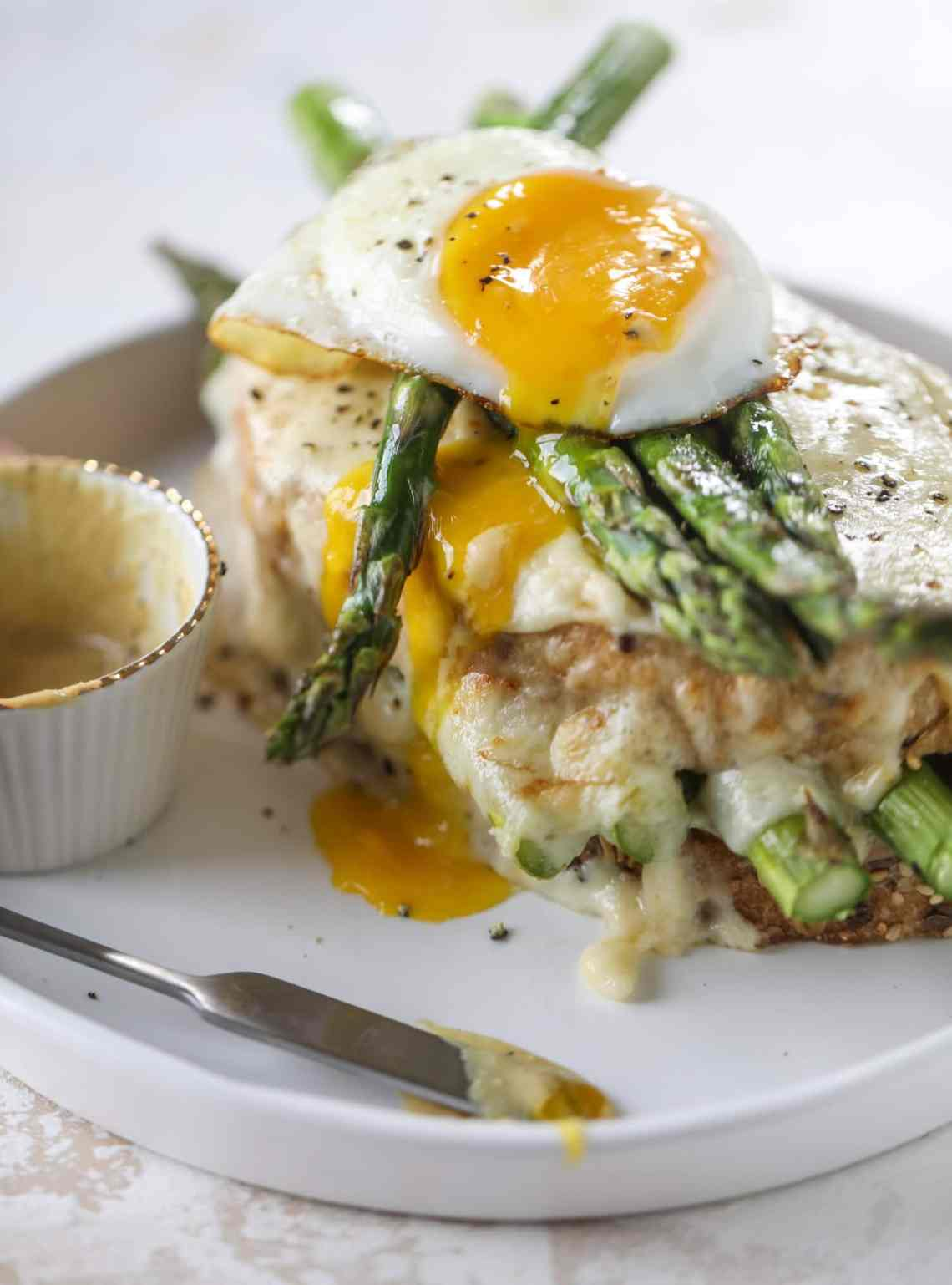 This roasted asparagus croque madame is made with thinly-sliced prosciutto and a fontina cheese sauce. Lots of dijon and an egg on top! I howsweeteats.com #croquemadame #asparagus