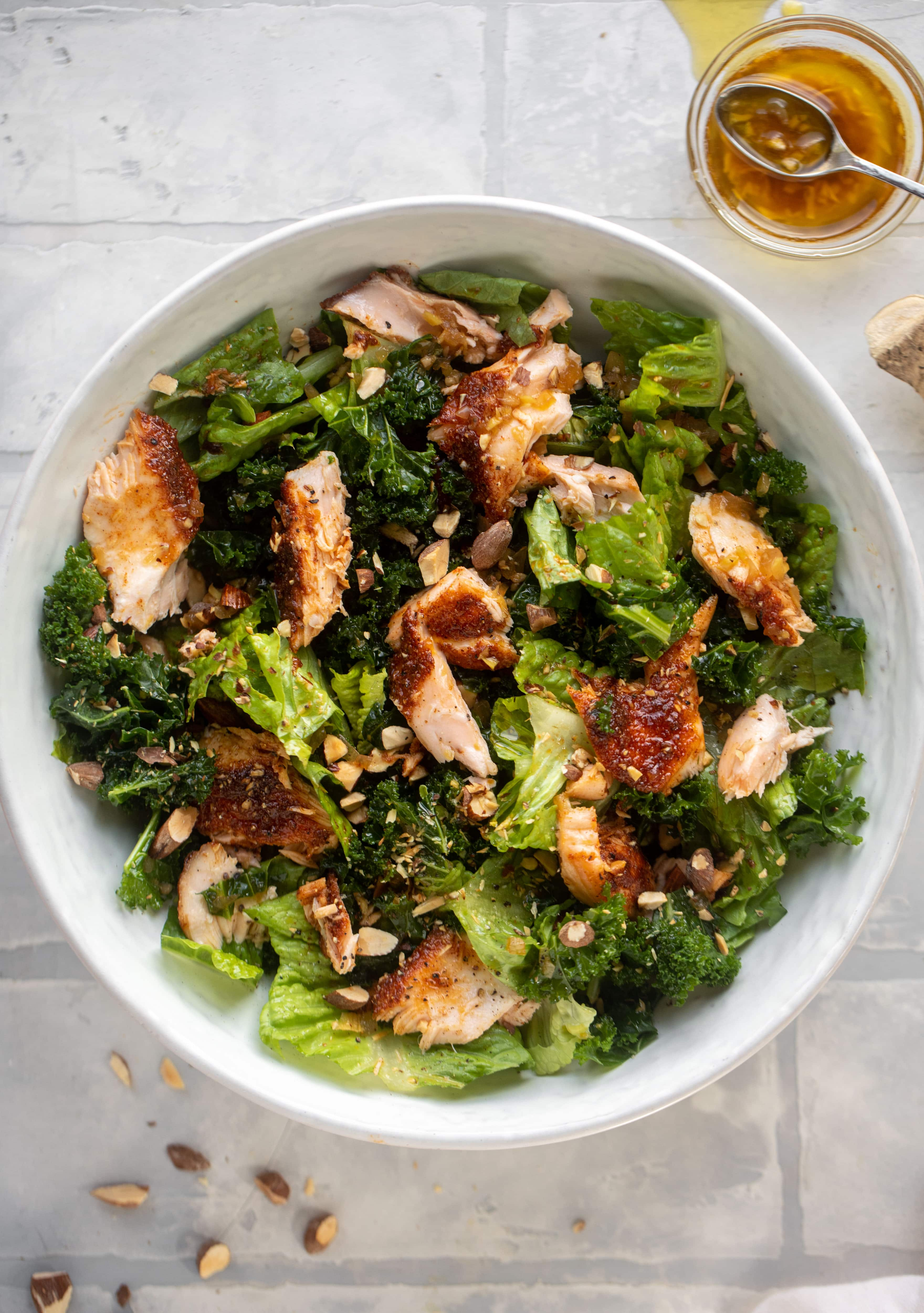 This ginger salmon salad has the flaky, flavorful roasted salmon on top of kale and romaine, drizzled with warm ginger vinaigrette.