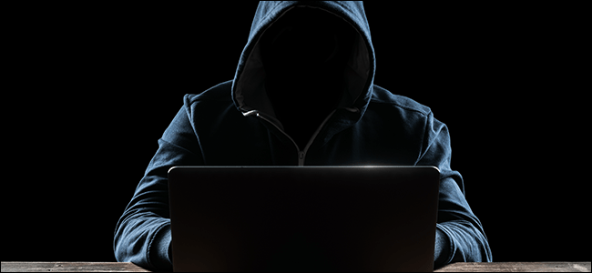 A hooded hacker in front of his computer