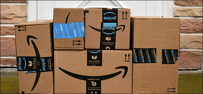 A stack of Amazon boxes at a front porch.