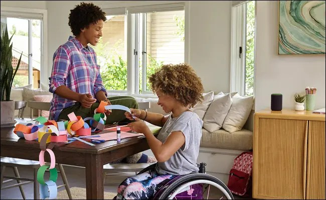 A young child in a wheel chair doing crafts with her mom at a table with an Amazon Echo nearby.