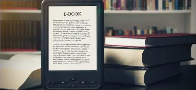 An e-book on an e-reader in front of books at a library.