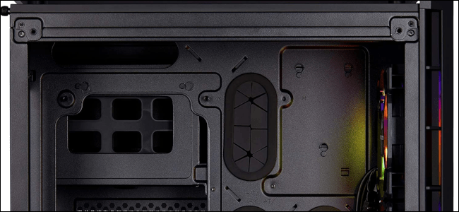 Close up of a Corsair PC case with rubber grommets for cable pass through.
