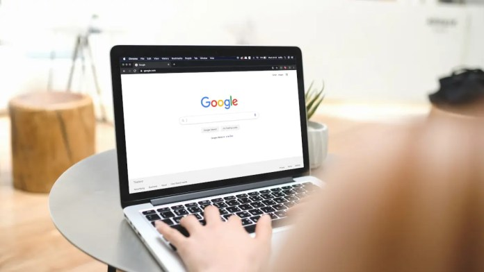 Woman typing on a laptop with Google search open in browser