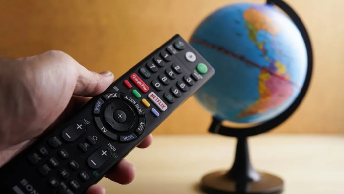 A remote control with a Netflix button pointed at a globe.
