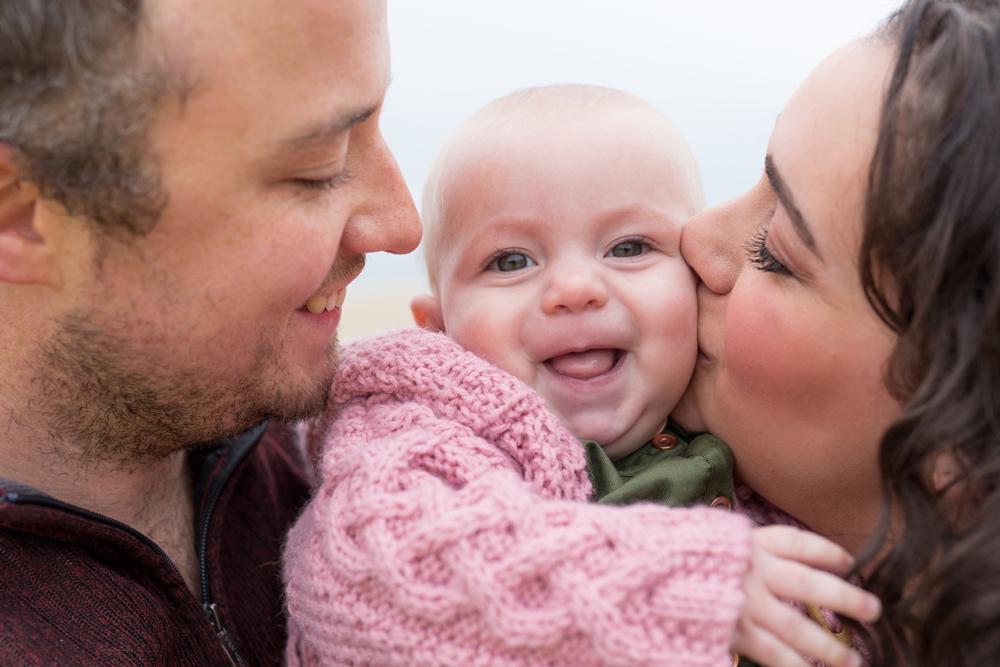 close up photo of parents kissing kids cheeks