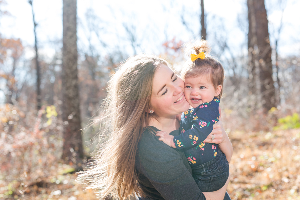 mom and daughter posing outdoors in fall