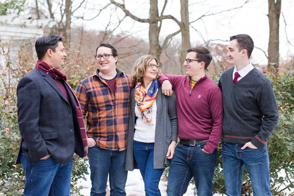 mom and four boys pose outdoors in snow