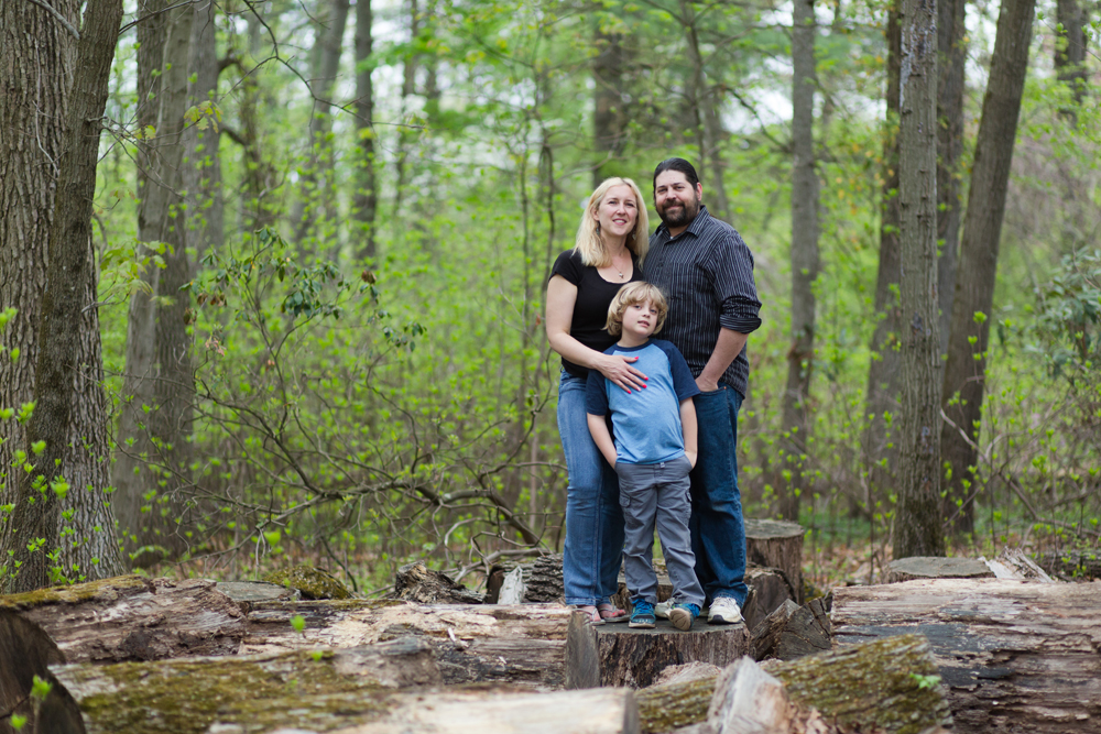 family of three posing in woods