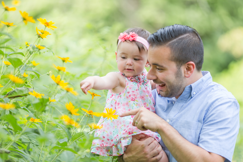 dad and daughter looking at flowers