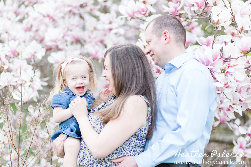 family poses and laughs in front of magnolia tree