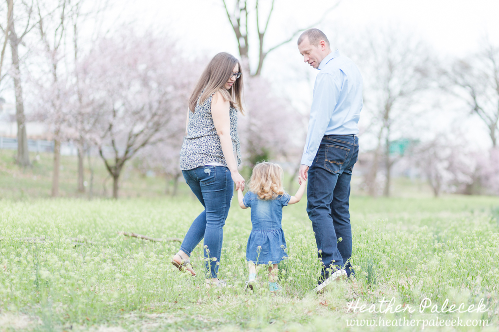 mom and dad hold hands and walk with daughter