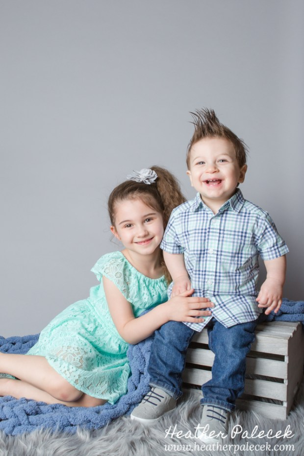 brother and sister portrait in studio with gray background