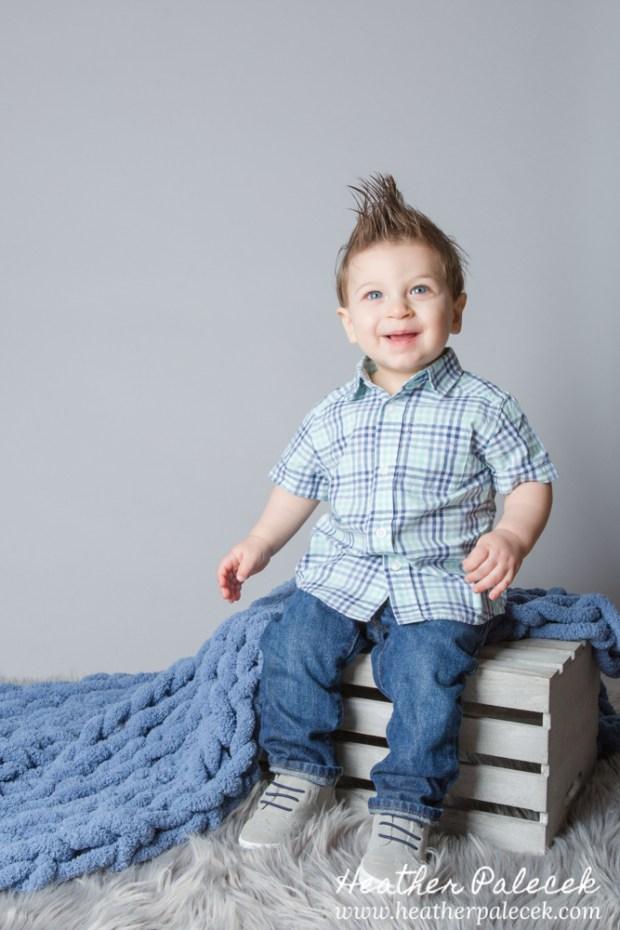 first birthday portrait of boy in blue button down