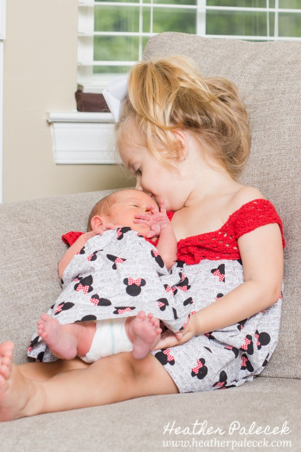 sister holding newborn in minnie mouse dress