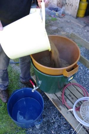 Slévání sladiny do scezovací nádoby
