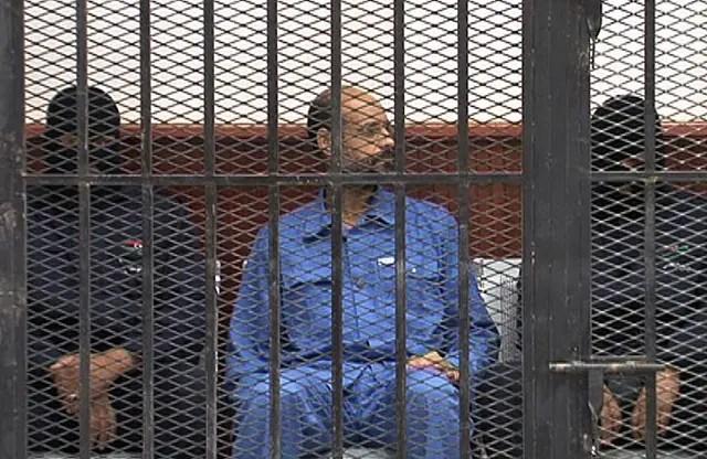 <p>Saif al-Islam, son of deposed strongman Muammar Gaddafi, sits behind bars during a court session in Zintan, Libya on May 2, 2013.</p>
