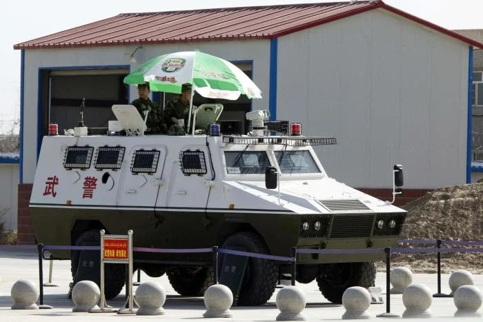 Two soldiers ride in an armored vehicle