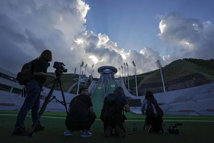 People with camera equipment standing in front of a venue for ski jumping