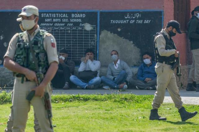 Indian paramilitary soldiers stand guard next to teachers at a government school where suspected militants fatally shot two teachers on the outskirts of Srinagar, India, October 7, 2021.