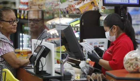 Grocery store cashier wears a mask while working