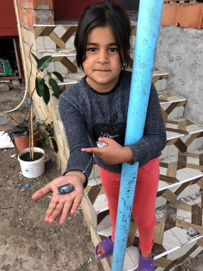 Uma jovem mostra um fragmento de munição para a câmera